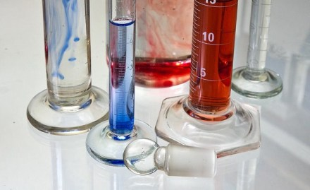 Several chemistry tubes made from transparent glass filled either with water or blue and red substances. Some of the recipients have white gradations used for measuring the quantities. They are on a reflective white surface.